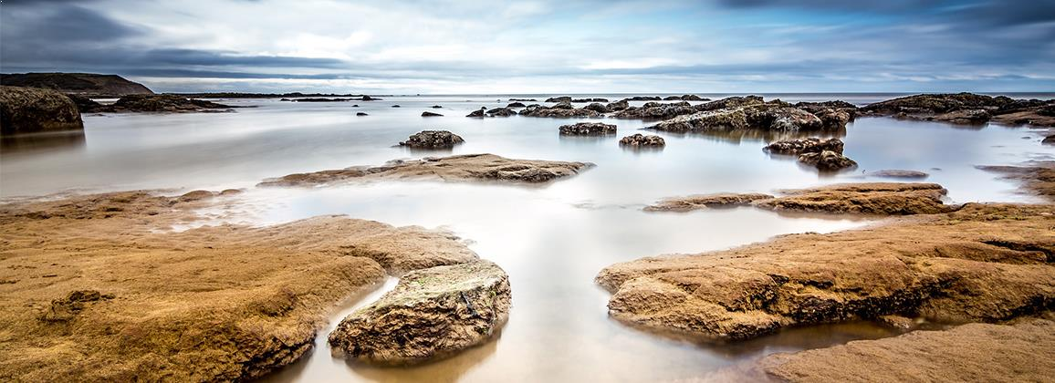 Ocean rock pools set against a blue sky